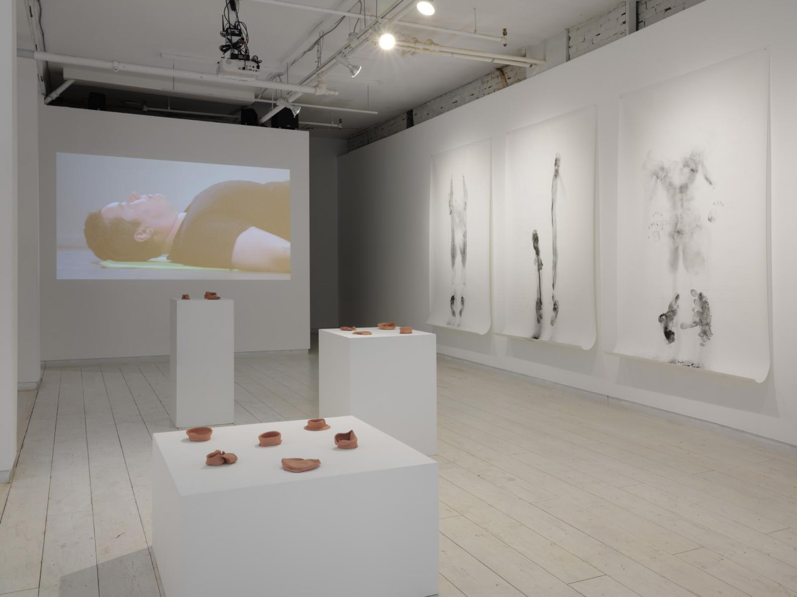 Installation view featuring three large drawings, a video of the artist lying on their back, and three plinths displaying unglazed ceramic forms.