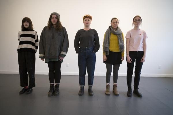 A group of people standing against a wall facing the camera