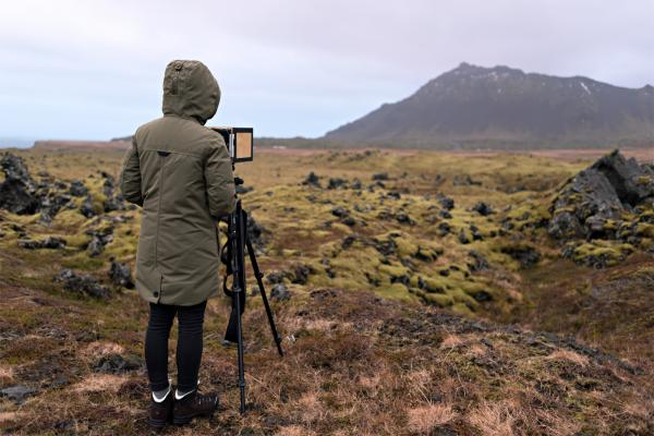 image of the artist and her camera, looking out at a lava field in Iceland.