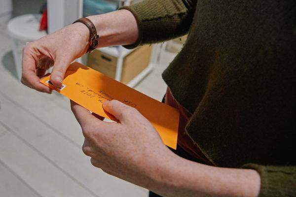 Two hands holding the postcards that are inside of a bright orange envelope, soon on their way to summerland.