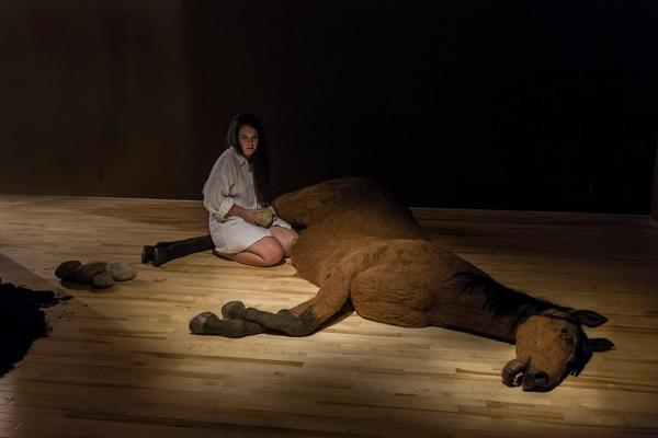 Artist Vicky Sabourin kneels on the floor beside a life-size, wool-felted brown horse. She is holding a medium sized stone which she has removed from an opening in the horses belly, and there is a pile of these stones beside her to the left. The artist is wearing an oversized smock, and the lighting is dim, with a spotlight shining on her and the horse.