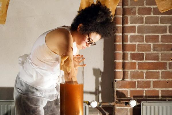 Artist Alanna Lynch in a brick studio space surrounded by fermented glove sculptures hanging on a clothes lines. She is reaching into a tall cylindrical glass vessel full of orange fermented liquid. The vessel of liquid is sitting on a wooden table beside glass bottles, some full some empty. The artist is wearing a thin apron, glasses, and has curly black hair. there is a radiator and an archway in the background, with sunlight filtering through from the right of the picture field.
