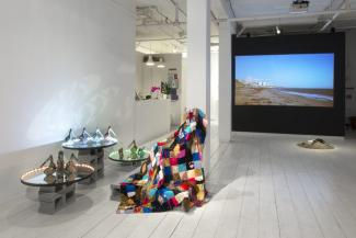 installation view of video, quilt, and ceramics shoes on a mirror platform installed in a gallery