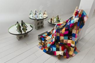 installation view of quilt, and ceramics shoes on a mirror platform installed in a gallery