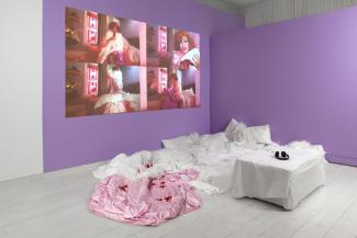 Installation view of feather boas, a video projection, and white seating installed in a purple corner of the gallery