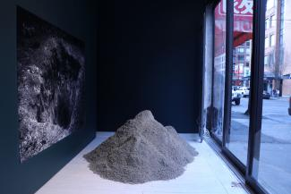 Installation view of pile of sand with photograph of hole in dirt.