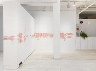 installation view of a long stencilled drawing in pink chalk ending at the administrative desk of the gallery
