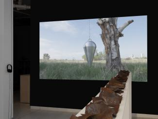 a video of a pendulum hanging from a tree, the projection framed by a dark wall, with a row of steel plates on a shelf