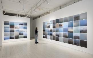 installation view of two large grids of photogs on adjacent walls, with a blurred figure observing