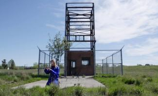 a video still of artist Alana Bartol kneeling on the grass in front of a fenced off orphan well