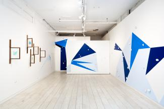 installation view of wall paintings with geometric shapes in various blues and sculptural objects