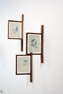 Installation view of framed drawings installed perpendicular to the wall