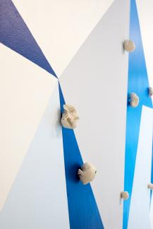 wall painting of geometric shapes in various blue tones, with ceramic sculptural objects