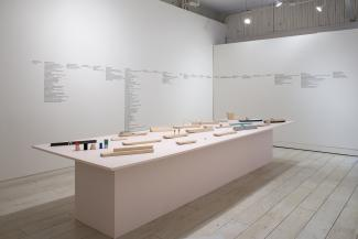 installation view of a long pale pink plinth and sculptural objects