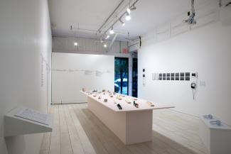 Installation views of sculptural objects on a long pale pink plinth