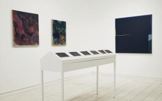 installation view of three dark paintings and a long white table
