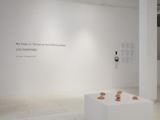 Installation view of the exhibition title on a wall, with a plinth displaying ceramics in the foreground