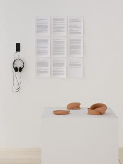 Installation view featuring a grid of nine documents on the wall, and an iphone with headphones installed to its left, with a plinth displaying unglazed ceramic forms in the foreground.