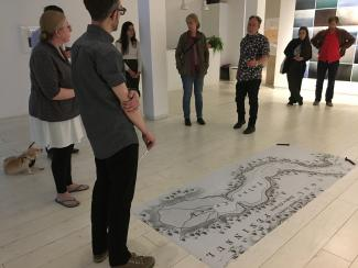 Artist Alex Grünenfelder stands in Access Gallery in front of a large black and white printed map laid on the floor with two train spikes on its corners. A small crowd of about 8 people, and one small dog, look on while Alex conducts his performance piece.