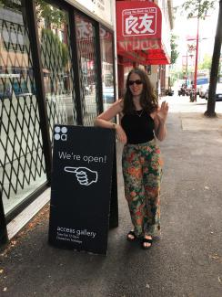 Smart and stylish woman wearing flower pants waving goodbye beside the gallery's open sign