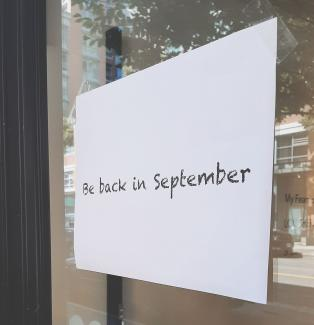 "A piece of paper taped to the front door of Access Gallery stating ""Be back in September""."