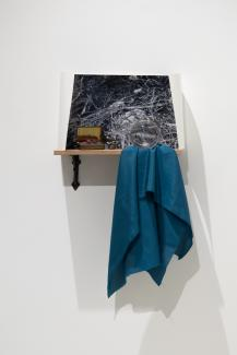 photograph, small treasures, a piece of blue fabric, installed on a small shelf