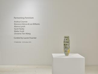 A ceramic vase on a plinth, with artists names on the wall behind
