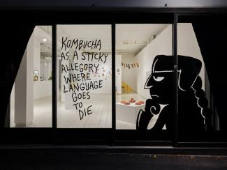 "View into the lit gallery at night, through a window with a figure and letting in black vinyl ""Kombucha is a sticky allegory where language goes to die"""