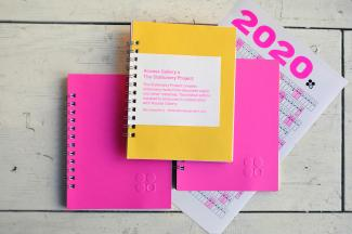 image of two pink and one yellow spiral bound notebooks and 2020 calendar