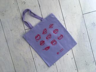 lavender tote bag with image of 9 mouths in a grid printed in red in