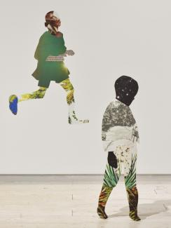 Installation of collaged work on the wall and extending into the space as 2D sculptures, featuring a small child standing, with a child running behind them