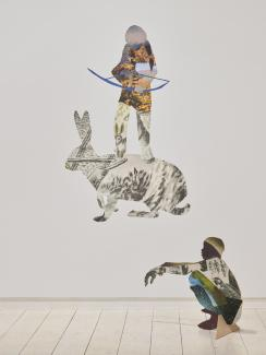 Installation of collaged work on the wall and extending into the space as 2D sculptures, featuring a hunter standing on a hare's back, and a crouching boy.